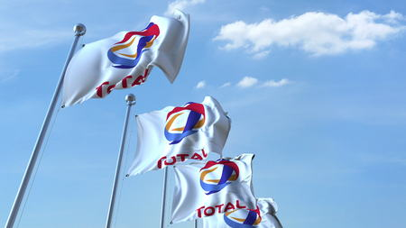 Waving flags with Total logo against sky, editorial 3D rendering 報道画像