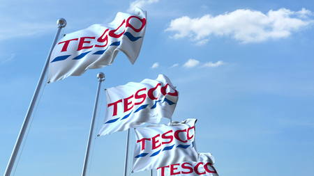 Waving flags with Tesco logo against sky, editorial 3D rendering 에디토리얼