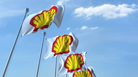Waving flags with Shell logo against sky, editorial 3D rendering