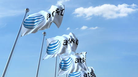 Waving flags with AT&T logo against sky, editorial 3D rendering