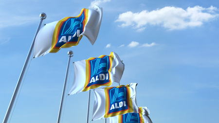 Waving flags with Aldi logo against sky, editorial 3D rendering Editorial