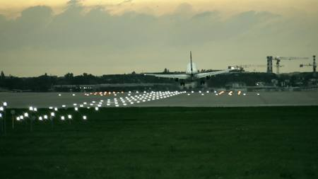 Twin engine commercial airplane landing at the airport in the evening, rear view Stock fotó