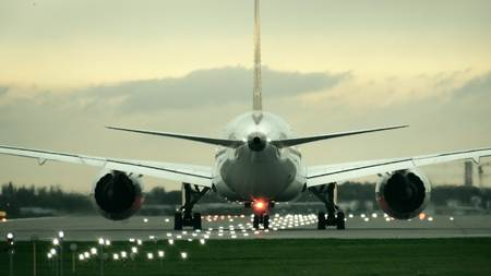 Twin engine commercial airplane starting takeoff from the airport in the evening, rear view