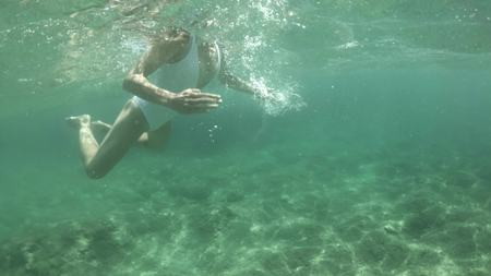 Underwater shot of a beautiful young woman in white swimsuit swimming in the sea