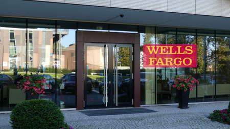 Glass facade of a modern office building with Wells Fargo logo. Editorial 3D rendering