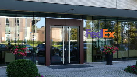 Glass facade of a modern office building with FedEx logo. Editorial 3D rendering