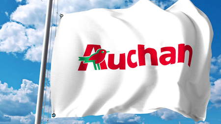 Waving flag with Auchan logo against clouds and sky. Editorial 3D rendering