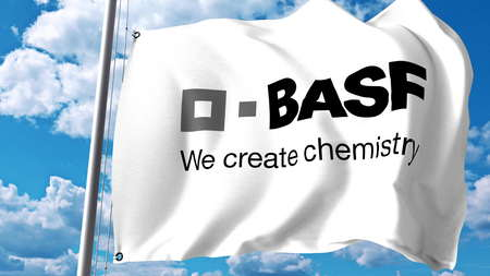 Waving flag with BASF logo against clouds and sky. Editorial 3D rendering