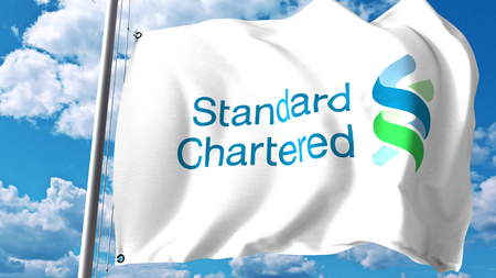 Waving flag with Standard Chartered logo against clouds and sky. Editorial 3D rendering Editorial
