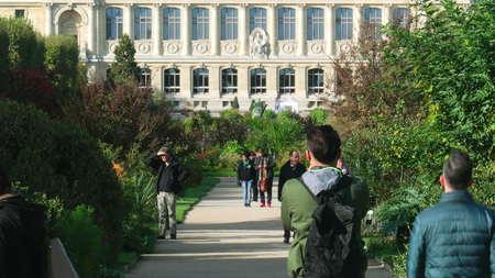 human evolution: PARIS, FRANCE - OCTOBER 8, 2017. Crowded Jardin des plantes alley, the main botanical garden and facade of the grande galerie de lEvolution or Gallery of Evolution