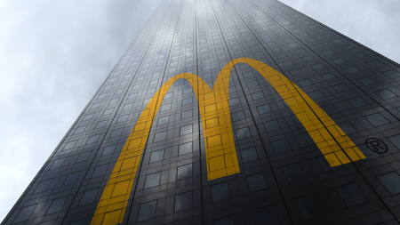 McDonalds logo on a skyscraper facade reflecting clouds. Editorial 3D rendering