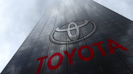 Toyota logo on a skyscraper facade reflecting clouds. Editorial 3D rendering