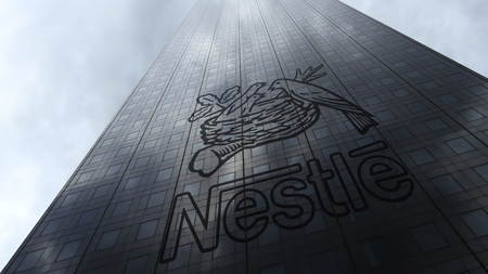 Nestle logo on a skyscraper facade reflecting clouds. Editorial 3D rendering Zdjęcie Seryjne - 87460789