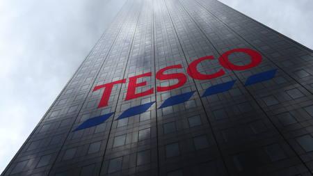 Tesco logo on a skyscraper facade reflecting clouds. Editorial 3D rendering Publikacyjne