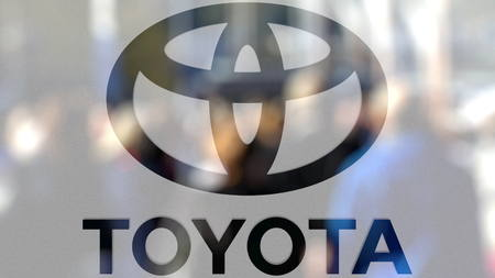 Toyota logo on a glass against blurred crowd on the steet. Editorial 3D rendering