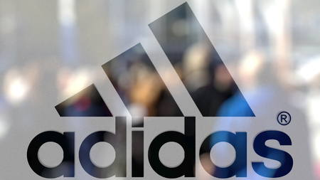 Adidas inscription and logo on a glass against blurred crowd on the steet. Editorial 3D rendering