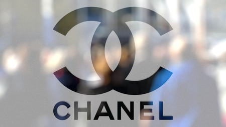 Chanel logo on a glass against blurred crowd on the steet. Editorial 3D rendering