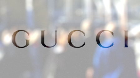 Gucci logo on a glass against blurred crowd on the steet. Editorial 3D rendering
