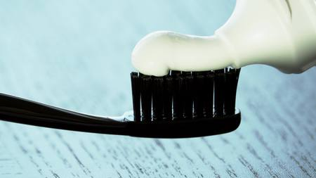 Toothpaste being squeezed onto the black toothbrush