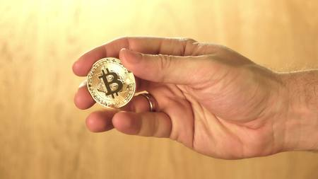 Man holding shiny bitcoin in his hand. Cryptocurrency concept