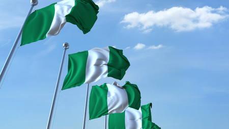 Multiple waving flags of Nigeria against the blue sky. 3D rendering
