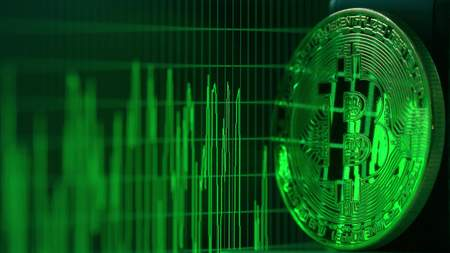 Shiny bitcoin reflects green data graph on the computer screen. Cryptocurrency related shot