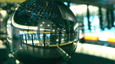 Unknown people walk in a modern shopping mall view through the glass ball Stock Photo