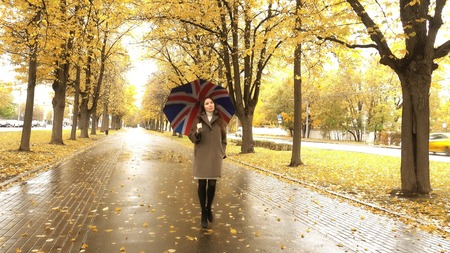 Beautiful pregnant woman walking with umbrella along autumn alley on a rainy day
