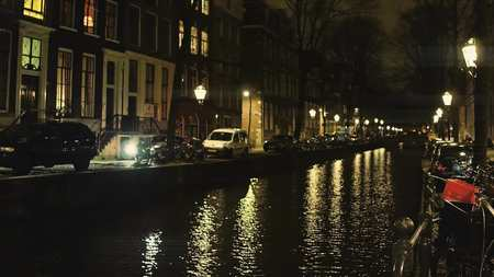 Typical Amsterdam canal and houses alongside embankment at night, the Netherlands