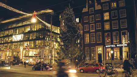 AMSTERDAM, NETHERLANDS - DECEMBER 28, 2017. Big decorated Christmas tree and night traffic on Rokin major street Editorial