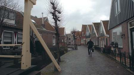 Unknown female cyclist riding along the street in a small Dutch town, Netherlands