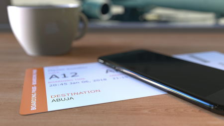 Boarding pass to Abuja and smartphone on the table in airport while travelling to Nigeria. 3D rendering Stock Photo