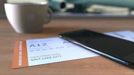 Instapkaart naar Salt Lake City en smartphone op de tafel in de luchthaven tijdens het reizen naar de Verenigde Staten. 3D-weergave