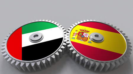 Flags of the UAE and Spain on meshing gears. International cooperation conceptual 3D rendering