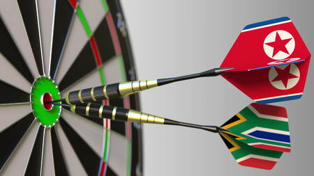 Flags of North Korea and South Africa on darts hitting bullseye of the target. International cooperation or competition conceptual 3D rendering Stock Photo