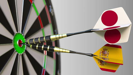 Flags of Japan and Spain on darts hitting bullseye of the target. International cooperation or competition conceptual 3D rendering