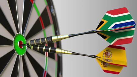 Flags of South Africa and Spain on darts hitting bullseye of the target. International cooperation or competition conceptual 3D rendering