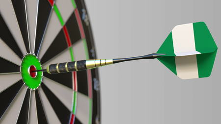 Dart featuring flag of Nigeria hits bullseye of the target. Sports or political success related conceptual 3D rendering
