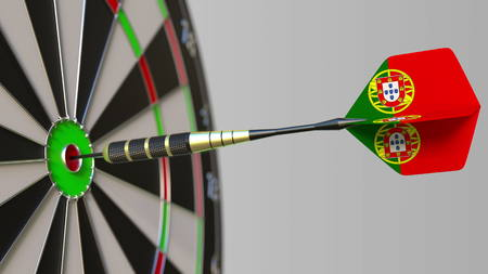 Dart featuring flag of Portugal hits bullseye of the target. Sports or political success related conceptual 3D rendering Foto de archivo