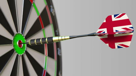 Dart featuring flag of the United Kingdom hits bullseye of the target. Sports or political success related conceptual 3D rendering Foto de archivo