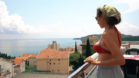 Beautiful woman looks at sea from the terrace on a summer day