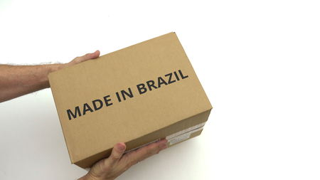 Man delivers carton with MADE IN BRAZIL text on it Banco de Imagens