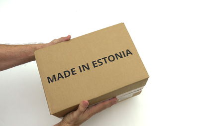 Man delivers carton with MADE IN ESTONIA text on it 免版税图像