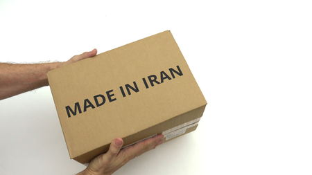 Hands holding box with MADE IN IRAN text on it Banco de Imagens