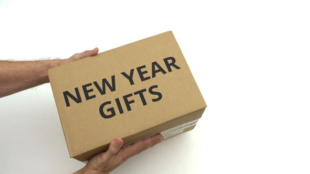 Man gives box with NEW YEAR GIFTS text on it Reklamní fotografie
