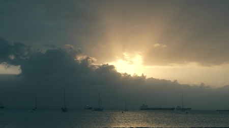 Time lapse of unknown anchored sailboats and cargo ships at sea near Gibraltar in the evening 免版税图像