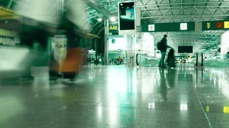 Unrecognizable passengers walk in generic airport terminal. Long exposure shot