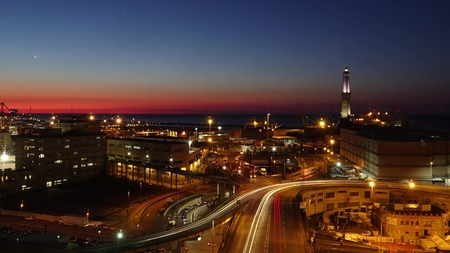 Lighthouse and city interchange traffic in seaport area of Genoa in the morning, Italy