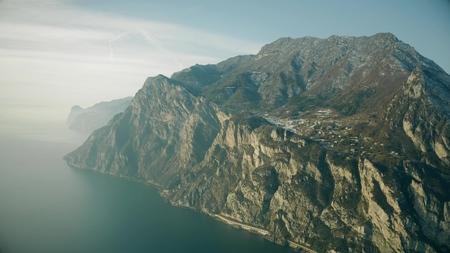 Aerial view of mountainous shore of the Lake Garda on a hazy day, Italy Stock Photo