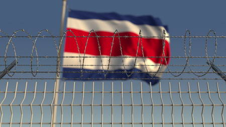Defocused waving flag of Costa rica behind barbed wire fence. 3D rendering Stock Photo